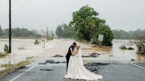 Newly-weds kissing in front of a flooded bridge near Sydney after they were brought to the church by helicopter. The bride, Kate Fotheringham, posted the picture online