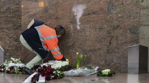 A Brussels Airport worker lays flowers at a memorial marking the one-year anniversary (AP)