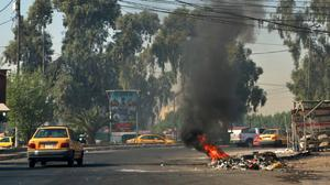 Motorists pass a fire lit by anti-government protesters in Baghdad (Khalid Mohammed/AP)