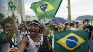 A demonstrator shouts slogans during a protest in support of Jair Bolsonaro at Copacabana beach in Rio de Janeiro. Brazil's president is hoping his far-right supporters help ensure his political survival amid unrest over the coronavirus (Leo Correa/AP)