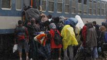 A group of migrants board a train as heavy rain starts to fall in Hungary (AP)