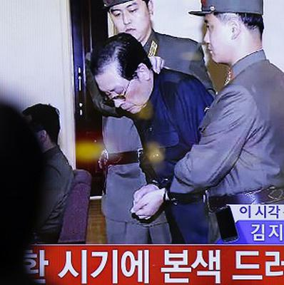 A man watches live news showing Kim Jong Un's uncle Jang Song Thaek being removed by military officers