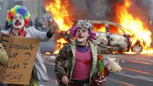 Demonstrators dressed as clowns pass by a burning police car in Frankfurt, Germany (AP)