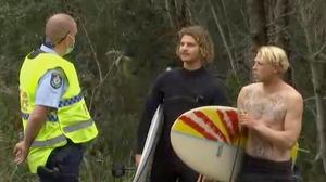 A policeman talks to surfers near the beach in Coffs Harbour, Australia, where a man was fatally bitten by a shark (Australian Broadcasting Corporation/AP)