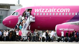 Passengers get on a Wizzair.com plane at Luton Airport (PA)