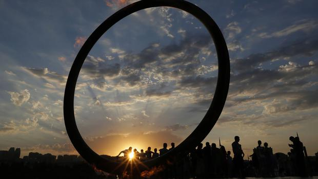 People walk near the giant ring with the flame of the 2015 European Games at the embankment of Caspian Sea in Baku, Azerbaijan (AP)