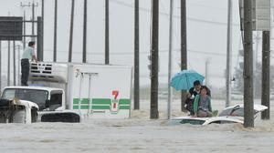 People wait for help as vehicles are submerged in flooding in Joso, Ibaraki prefecture, north east of Tokyo. Heavy rain pummelled Japan for a second straight day, overflowing rivers and causing landslides and localised flooding in the eastern part of the country. (Kyodo News via AP)