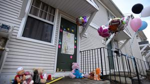 Stuffed animals, balloons, and notes are left outside the Detroit home where two children's bodies were found (The Ann Arbor News-MLive.com Detroit/AP)