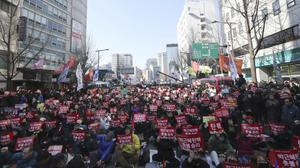 Protesters shout slogans during a rally near the Constitutional Court in Seoul, South Korea (Lee Jin-man/AP)