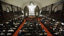 Parishioners sit at the Emanuel AME Church four days after a mass shooting that claimed the lives of its pastor and eight others (AP)