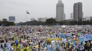 Thousands of the faithful wait in the rain at Rizal Park where Pope Francis will celebrate his final Mass in Manila, Philippines (AP)