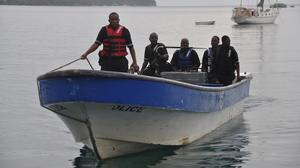 Jamaican Marine Police return to the Port Antonio Marina after a fruitless search for the plane (AP)