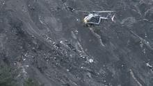 A recue helicopter flies over debris of the Germanwings passenger jet in the French Alps (AP)