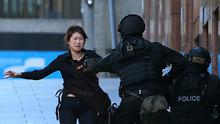 A hostage runs to armed tactical response police officers for safety after she escaped from the Lindt Cafe siege (AP)