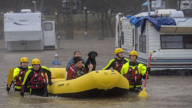 A fire department's water rescue team brings a couple and their three dogs to safety in Bristol, Tennessee (Andre Teague/Bristol Herald Courier via AP)
