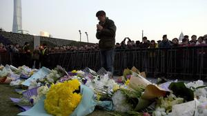 A man prays after laying flowers at the site of the deadly stampede in Shanghai (AP)