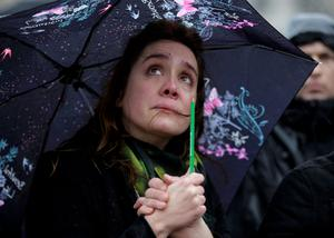 A woman holding a pencil cries as she gathers in front of the Notre Dame Cathedral in Paris for a minute's silence. Photo:  Reuters
