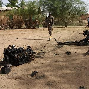 Soldiers walk near debris after suicide bombers blew themselves up inside a military barracks, in Agadez, northern Niger (AP)