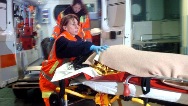 A woman is carried by paramedics (AP)