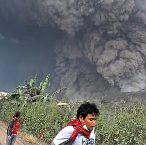 Villagers and a journalist prepare to flee as Mount Sinabung releases pyroclastic flows during an eruption in Namantaran, north Sumatra, Indonesia (AP)