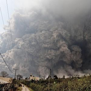 Mount Sinabung releases pyroclastic flows during an eruption as seen from Namantaran, north Sumatra, Indonesia (AP)