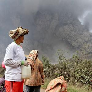 Villagers watch as Mount Sinabung releases pyroclastic flows during an eruption in Namantaran, north Sumatra, Indonesia (AP)