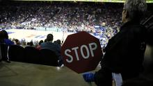 An usher at the Wells Fargo Center holds a Stop sign during an NBA basketball game between the Philadelphia 76ers and the Detroit Pistons on Wednesday (Matt Slocum/AP)