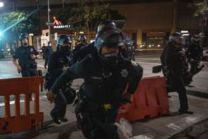 Police chase after protesters who refused to disperse in Oakland, California (Christian Monterrosa/AP)