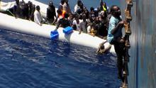 Migrants on a sinking rubber boat clamber up ropes and a ladder from the cargo ship Zeran that came to their aid (AP)