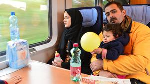 Eight-month-old Maria, her father Ibrahim and mother Yasmin on the train from Salzburg to Munich (AP)