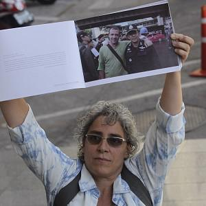 Elisabetta Polenghi, younger sister of shot Italian photographer Fabio Polenghi, holds up a book of his work outside a Thai court (AP)
