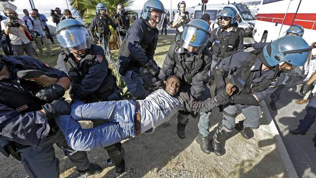 A migrant is removed by Italian police at the Franco-Italian border near Menton, southeastern France (AP)