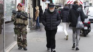 A soldier patrols outside a synagogue in Paris (AP)