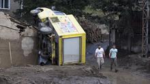 Volunteers walk past an overturned truck after Sunday's flooding in Tbilisi (AP)
