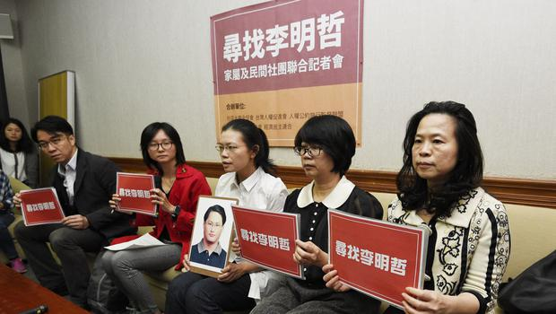 Lee Ching-yu holds up a photo of her missing husband and Taiwanese pro-democracy activist Lee Ming-che. (AP)