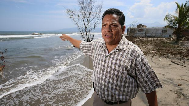 Biologist Gustavo Cabrera shows how much sea levels have risen