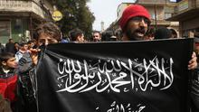 Anti-Syrian president Bashar Assad protesters hold the Jabhat al-Nusra flag as they shout slogans during a demonstration in Idlib province, northern Syria (AP)