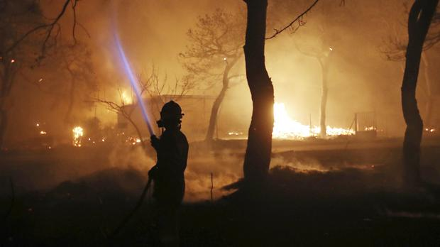 A firefighter sprays water on the fire in the town of Mati (AP Photo/Thanassis Stavrakis)