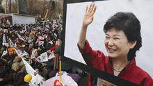 A supporter holds a picture of South Korean President Park Geun-hye during a rally opposing her impeachment in Seoul (AP/Lee Jin-man)
