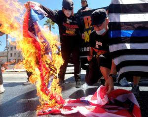 Defiant: Gregory Johnson (right), whose burning of an American flag in 1984 led to a Supreme Court ruling upholding the act as free speech, sets fire to one in LA. Photo: Reuters