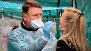 HSE paramedic Andrew Connaughton conducts a Covid swab on Charlotte Lynch, at the HSE walk-in Covid test centre at Castletown House in Celbridge (Picture: Frank McGrath)