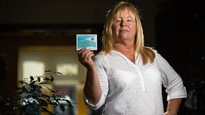 Philomena Meredith holding her vaccination card.