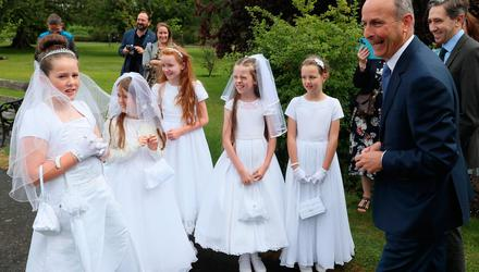 Taoiseach Micheál Martin meets pupils from St. Brigid's Girls NS in Glasnevin, Dublin - Isabella Ryan (10), Ella Brereton (9), Charlotte Collins (9), Caoimhe Flanagan (10), and Faye Haverty (10) - who made their first holy communion. Photo: Brian Lawless/PA