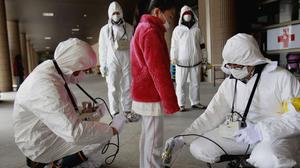 A young evacuee is screened at a shelter for leaked radiation from the tsunami-ravaged Fukushima Dai-ichi nuclear power plant in 2011 (Wally Santana/AP)