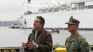 New York Go. Andrew Cuomo, left, speaks as he stands beside Rear Adm. John B. Mustin after the arrival of the USNS Comfort, a naval hospital ship with a 1,000 bed-capacity, Monday, March 30, 2020, at Pier 90 in New York. The ship will be used to treat New Yorkers who don't have coronavirus as land-based hospitals fill up with and treat those who do. (AP Photo/Kathy Willens)
