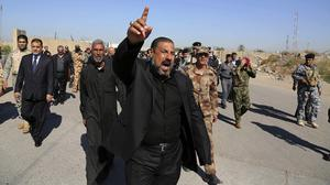 Mourners chant anti-Islamic State group slogans during the funeral procession of police Lt Gen Faisal Malik in Baghdad (AP)