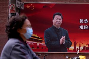 Facing up: A woman wearing a mask walks past a poster of Chinese President Xi Jinping in Shanghai. Photo: Aly Song