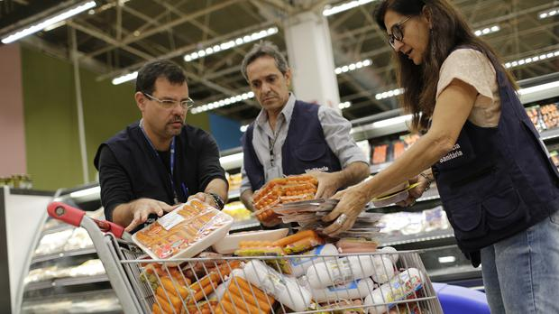 Workers from Municipal Sanitary Surveillance confiscate hot dogs to be analysed at a supermarket in Rio de Janeiro, Brazil (Silvia Izquierdo/AP)