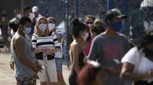 People queue for a Covid-19 test in Duque de Caxias, Brazil (AP/Leo Correa)