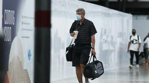 A traveller wears a face mask while walking through the main terminal of Denver International Airport (AP)